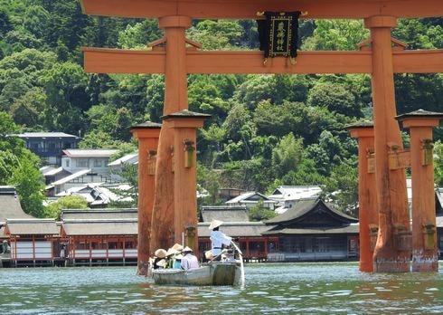 宮島の鳥居の下をくぐる船や遊覧船も
