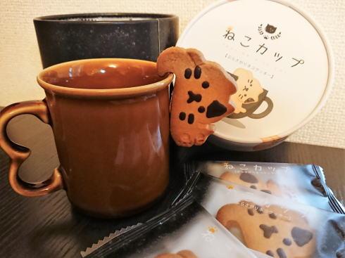 ねこカップ、コーヒーカップにぶら下がり癒すクッキー