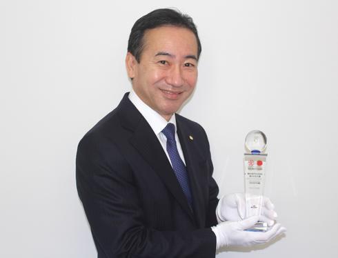 食かける大賞 受賞トロフィーを手にする、オタフクソースの佐々木孝富社長